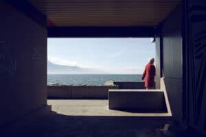 Dame au manteau rouge devant le lac Leman